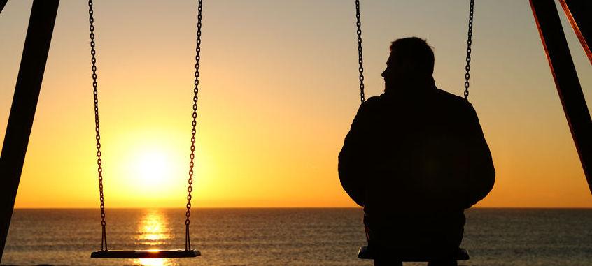 Man at sunset on swing